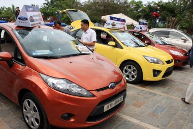 Visitors look at Ford cars during an auto show in Sanya city, south Chinas Hainan province, 8 April 2011