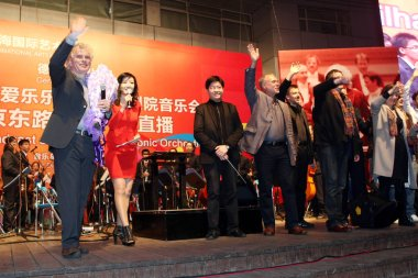 Sir Simon Rattle, left, principal conductor of the Berlin Philharmonic, waves to spectators after the live broadcast of the concert of the Berlin Philharmonic on the Nanjing Road shopping street in Shanghai, China, 13 November 2011
