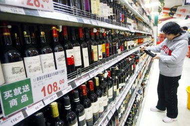A customer shops for red wine imported from France at a supermarket in Shanghai, China, 15 December 2010