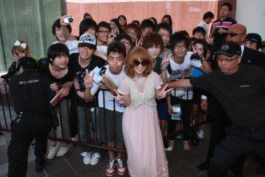 Japanese singer Ayumi Hamasaki poses with fans outside the hotel before leaving Hong Kong for Japan in Hong Kong, China, 1 July 2010.