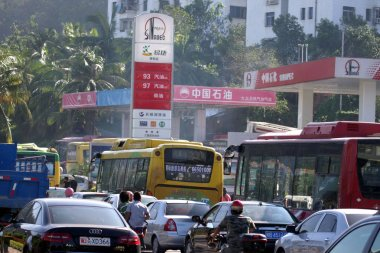 A long queue of cars and buses to be refuelled wait outside a Sinopec gas station in Sanya city, south Chinas Hainan province, 20 July 2010