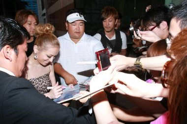 Japanese pop singer Ayumi Hamasaki signs for fans outside the hotel before going shopping for tea leaves in Hong Kong, China, 30 June 2010.