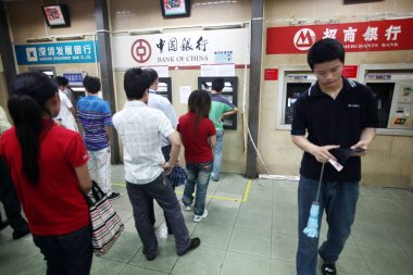 Chinese Foxconn employees queue up to draw money from ATMs at the Foxconn Shenzhen plant in Shenzhen city, south Chinas Guangdong province, 11 May 2010