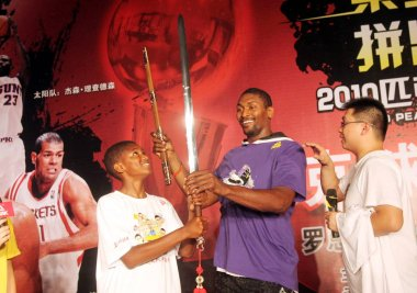 NBA basketball player Ron Artest of the Los Angeles Lakers, center, plays sword next to his son Jerron, left, during a meeting with Chinese fans in Wenzhou city, east Chinas Zhejiang province, 1 August 2010.