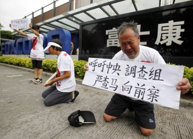 Parents and elder sister of Foxconn employee Ma Xiangqian who committed suicide by jumping off a building, show the photo of Ma Xiangqian and signs saying We Appeal To the Investigation Team from the Central Government to Thoroughly Investigate the C