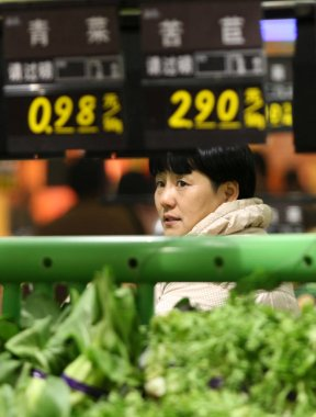 A Chinese customer shops for vegetables at a supermarket in Huaibei city, east Chinas Shandong province, 11 December 2010