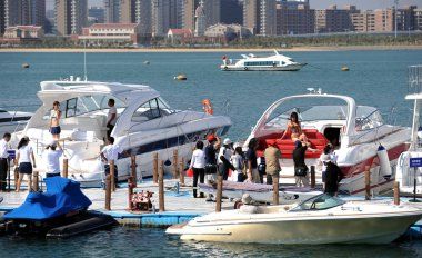 Chinese visitors take pictures of models on yachts on display during the 2009 China Xiamen International Boat Show in Xiamen city, southeast Chinas Fujian province, 31 October 2009