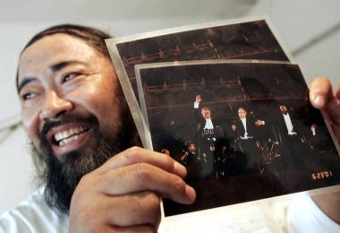 Mr. Jin, 52, shows photos of Luciano Pavarotti, Placido Domingo and Jose Carreras performing at a concert during a memorial meeting for the death of Italian tenor Luciano Pavarotti at his house in Tianjin 6 September 2007