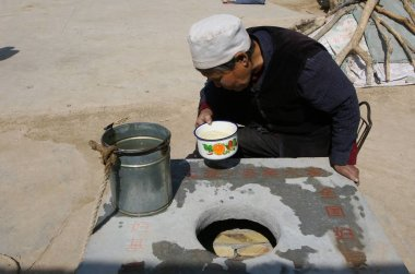 A local prepares to drink water loaded from a water well  as a prolonging drought hits Laoya Village, Touzhai Town, Huining County of northwest Chinas Gansu province, March 21, 2007