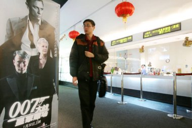 A Chinese man walks by the advertising poster of new James Bond (007) movie Casino Royale in Kodak Cinema World in Shanghai 2 February 2007. It is the first time for James Bond film screened in public in China