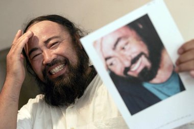 Mr. Jin, 52, imitates Italian Tenor Luciano Pavarotti during a memorial meeting for the death of Pavarotti at his house in Tianjin 6 September 2007
