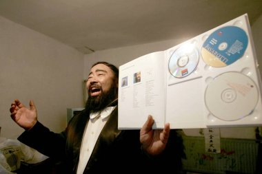 Mr. Jin, 52, dressed like Italian tenor Luciano Pavarotti, sings during a memorial meeting for the death of Pavarotti at his house in Tianjin 6 September 2007