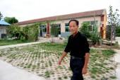 Kínai mezőgazdasági termelő hu Zhenqiang sétál korábbi házai az ő körte Farm Bajia Village, Beizangcun Town, Daxing District, Peking, Kína, szeptember 8, 2009.
