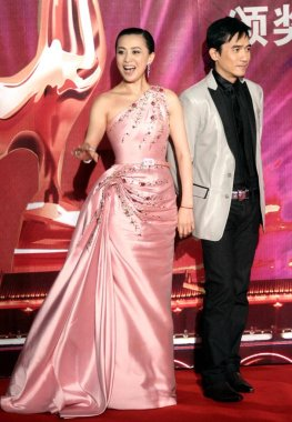 Hong Kong actress Carina Lau (left) and Hong Kong actor  Tony Leung pose during the closing ceremony of Golden Rooster and Hundred Flowers Film Festival, in Suzhou, east Chinas Jiangsu province, October 27, 2007.