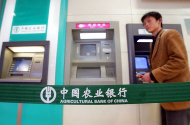 A Chinese man walks past ATMs at a branch of Agricultural Bank of China (ABC) in Guangzhou city, south Chinas Guangdong province, 3 March 2006
