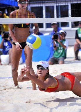 Chinas Xue Chen dives to return the ball to Chinas Tian Jia and Wang Jie during a semifinal match of womens beach volleyball, at Beijing 2008 Olympic Games, at Beijings Chaoyang Park Beach Volleyball Ground, in Beijing, August 19, 2008.