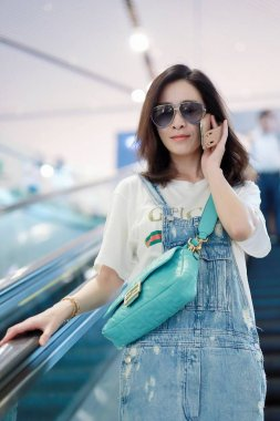 Charmaine Sheh Sze-man, a Hong Kong actress best known for acting in many television series produced by TVB since 1998, shows up livelily with Gucci T-shirt and blue overalls in an airport in Shanghai, China, 19 August 2019