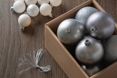 background of christmas decor from balls on a wooden table in a cardboard box
