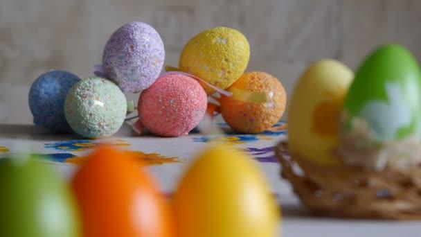 Close-up. Svíčky vyrobené ve tvaru velikonočního vajíčka. Velikonoční vejce svíčky a barevná krasová vajíčka na pozadí. Soustředění.