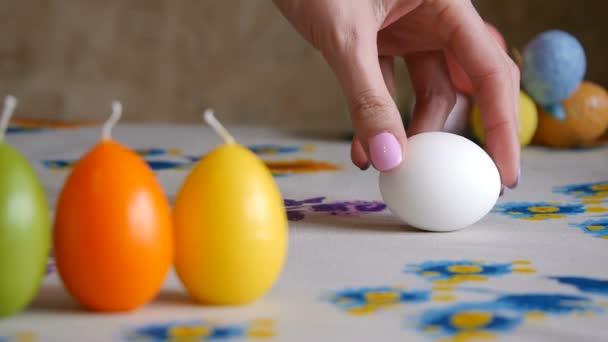 Húsvéti. Női kéz spin fehér tojást az asztalra. Színes húsvéti tojások a háttérben.