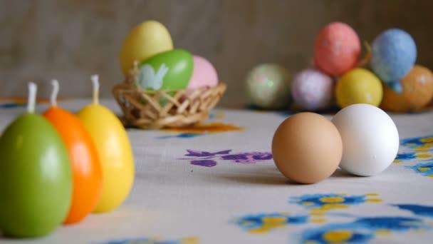 Kellemes húsvéti ünnepeket. férfi kézzel fordul a fehér csirke tojás az asztalra. olorful húsvéti tojások a háttérben.