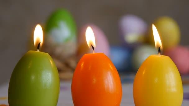 Kerzen in Form von Ostereiern. brennende Kerzen. grün, orange, gelb. Ostereierkerzen und bunte Ostereier im Hintergrund.