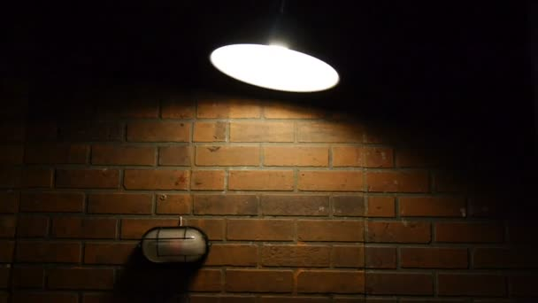Loft style ceiling light turned on swinging side to side. Filmed with studio light on a brick wall background. Lamp in the dark