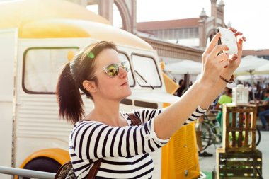 Young woman making a selfie, next to the vintage style food truck, at an outdoor even