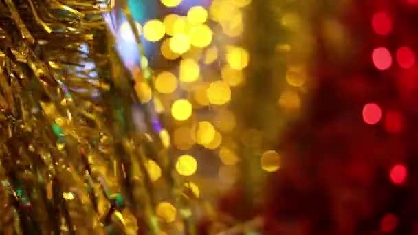 Veselé Vánoce a nový rok. Zlaté vánoční pozlátko věnec dekorace vlající ve větru. Rozmazané světla vánoční blikající na pozadí.