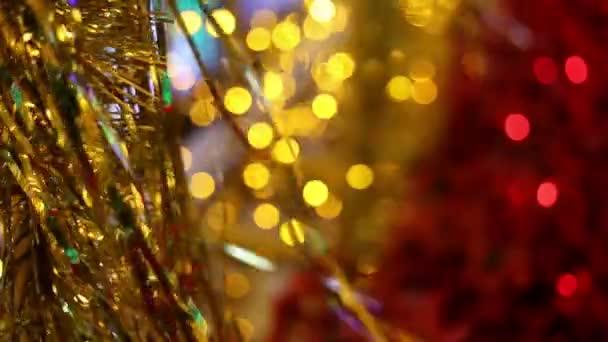 Karácsonyi és újévi ünnep ünnepe. Arany karácsonyi talmi koszorú díszek fúj a szél. Homályos karácsonyi fények villogó a háttérben.