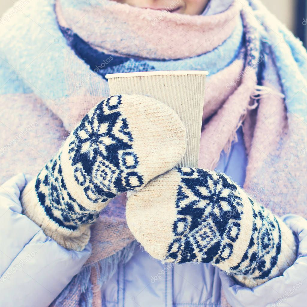 Female hands in white and black mittens holding steaming  cup of hot coffee cocoa, mulled wine or tea, outdoor. Winter time concept. Bask in the cold. Women's hands in mittens hold a craft paper glass