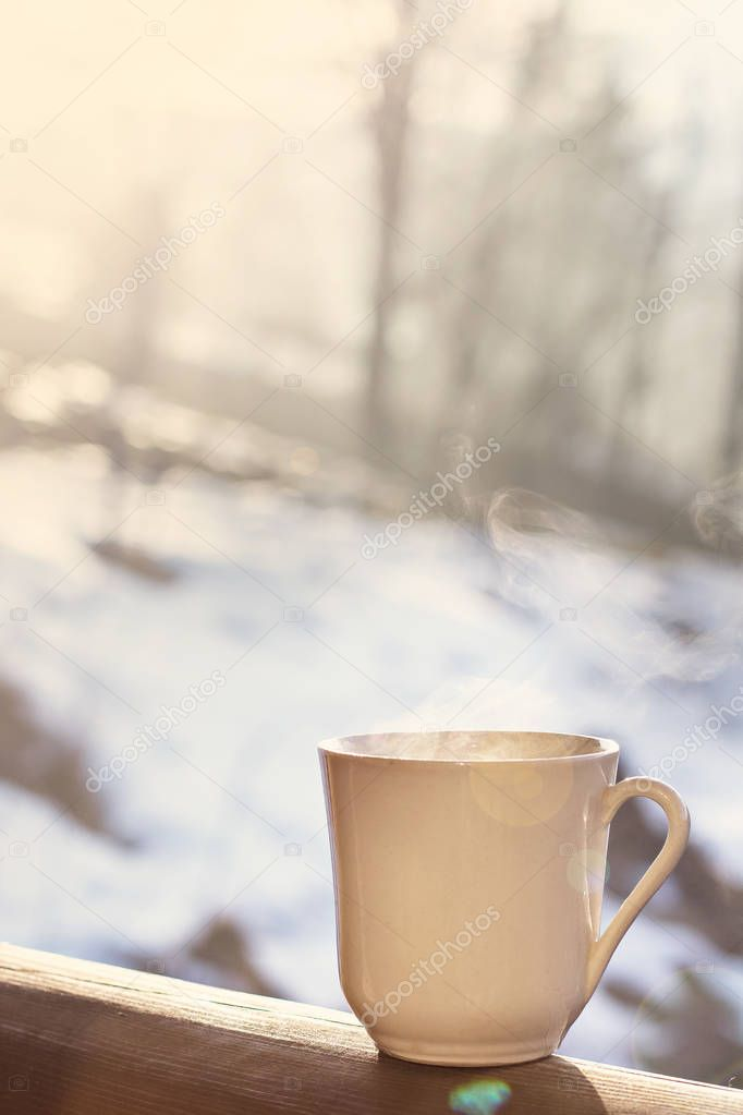 Cup with coffee, tea on the background of the winter landscape.  A cup with a hot drink on the background of the winter forest. the table outdoor in the winter. Winter time concept.