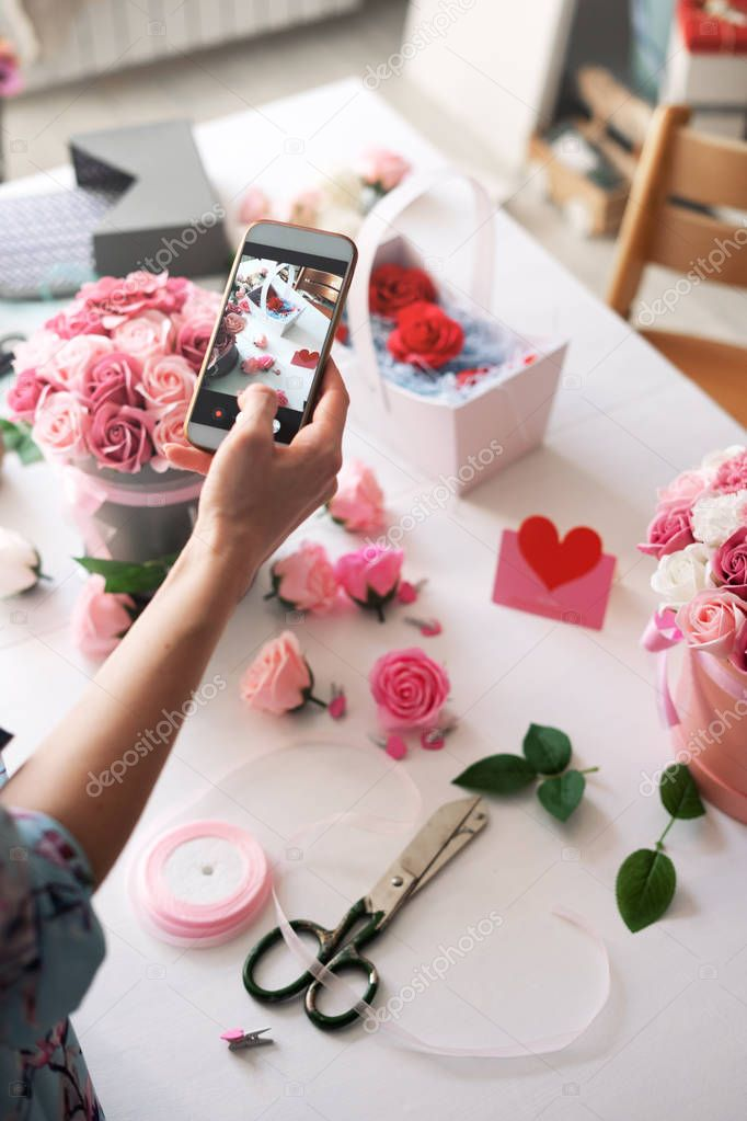 Flower shop: a girl florist collects a bouquet in a basket and photographs it on a smartphone for social networks.