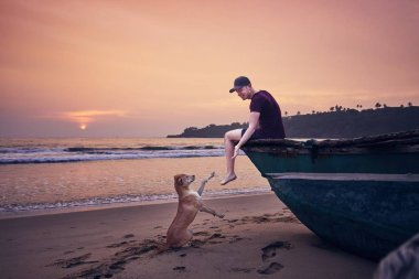 Young man relaxing on the beach and cheerful dog him giving paw at the sunrise. Tangalle in Sri Lanka.