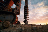 Photo Building activity on contruction site. Close-up view of drilling machine.