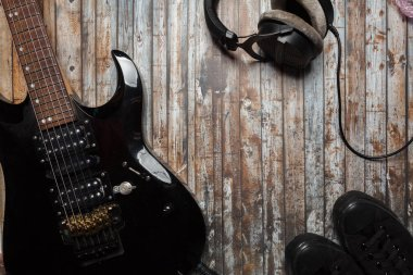 guitar on a wooden background with headphones