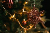 Fotografie Decorations on Christmas tree, garland lights and snowflake toy