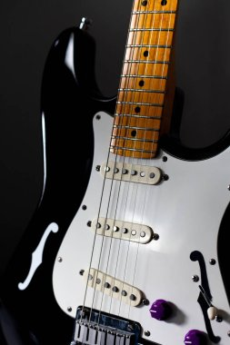 black white electric guitar in front of dark background
