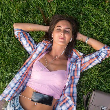 Relaxed young woman with headphones listening to music from a smartphone and lying on the grass her eyes closed