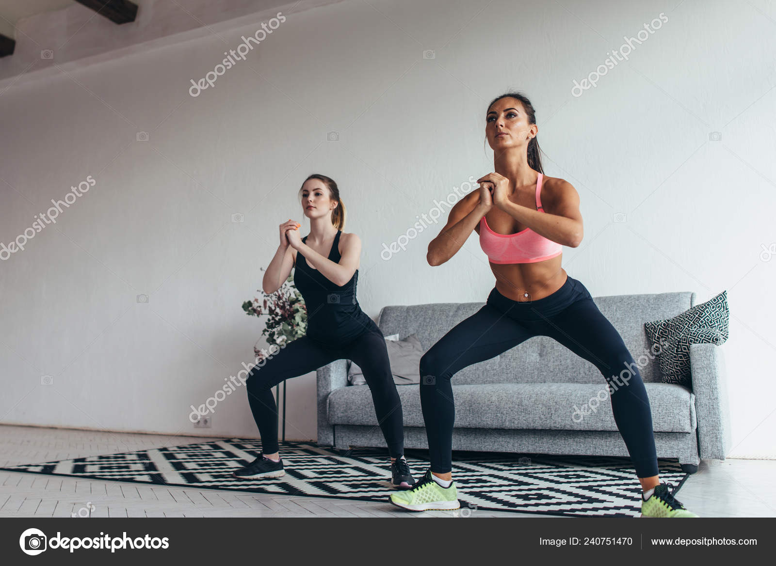 Two fit women exercising together doing squats at home