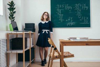 Sad schoolgirl standing in front of blackboard stock vector