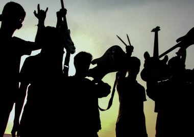 Silhouette of a group of teenagers from a band celebrating after their performance