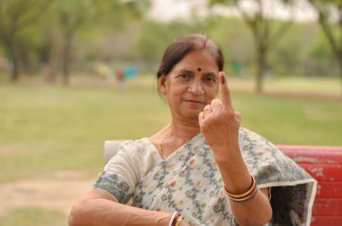 Senior Indian woman sitting on the red bench in a park and showing their inked finger after casting their vote in Indian assembly election in New Delhi, India