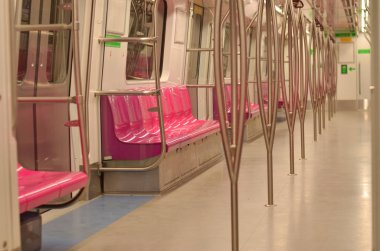 Pink seats in Empty Ladies / Women coach of  Delhi Metro Magenta line with pink seats at night. There's metro in many cities in India in Lucknow, Hyderabad, Kolkata, Jaipur, Bangalore, Mumbai, Chennai