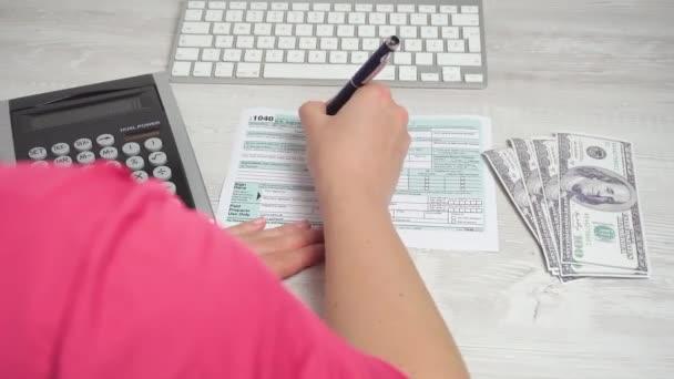 Přes rameno záběr žena naplnění daňových tvoří 1040 na stole vedle klávesnice počítače a Kalkulačka. 4k video