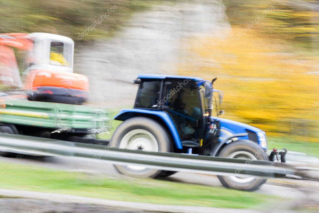 Tractor with a trailor in full speed motion passing by
