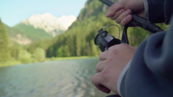 slow motion close up of a man holding a fishing rod and reel or angler on a sunny day near lake. With mountain and lake in the back