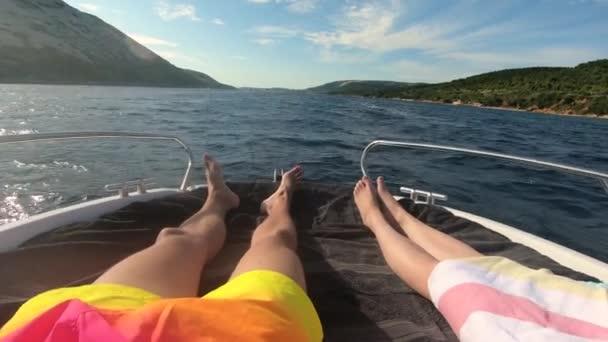Pohled na muže a ženu nohy kladení a jízdy na jachtě s tirquoise modré moře a pláž se zelenými palmami na pozadí. luxusní letní dovolená koncept.