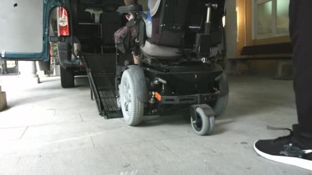 Járműrámpát használó kerekesszékes férfi