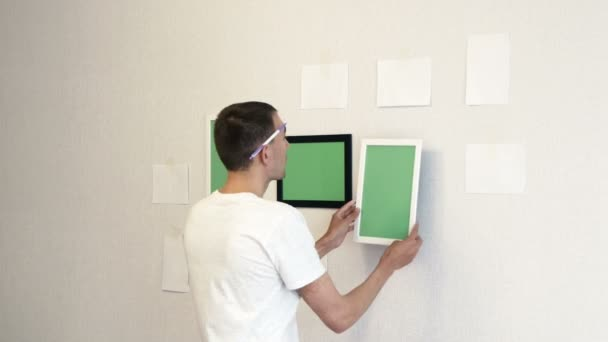 Young man sets a white photo frame on a wall. Man marks a place for a photo frame on the wall.